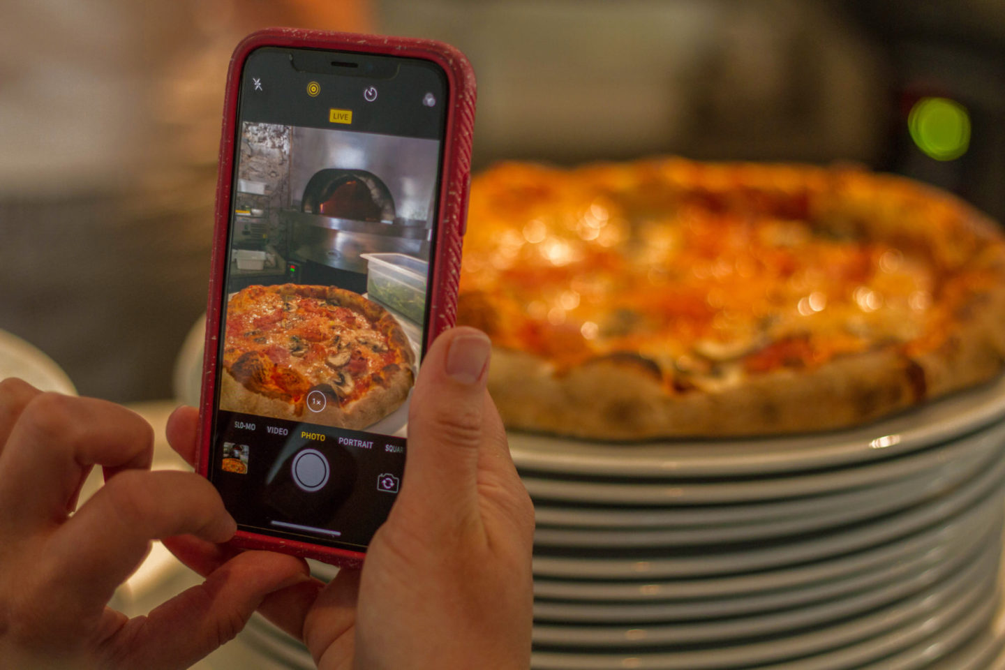 iPhone X being used to take picture of pizza